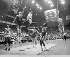 Black and white photo of University of Oregon basketball player Ronnie Lee challenging UCLA's Bill Walton as he puts up an inside shot during a game played at McArthur Court between 1972 and 1974. An unidentified Duck, wearing number 23, watches from the weak side. ©University of Oregon Libraries - Special Collections and University Archives