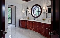 Master bathroom with brown cherry furniture and marble floor