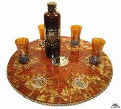 A Baltic amber carved set. Our first thought for using amber is for making highly desirable natural jewelry. Or for marveling over captured fossil specimens. But here a lot of fine quality Baltic amber is fashioned into a decorative platter with matching glasses for serving Latvian shots.