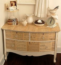 Seeing the potential:  Missing, chipping, and bubbled veneer went bye-bye, hidden forevermore under paint and… sheet music! The end result maximizes the dresser's pretty shape while masking the flaws like chips and bubbles. It's win-win, and fairly simple to do, too.