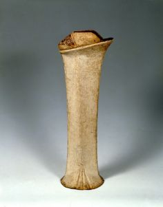 An extremely tall Venetian chopine made from wood covered in white leather with minimal ornamentation.