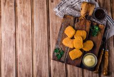 Chicken Nuggets on wooden cutting board with ketchup and sauce, on wooden background. Selective focus. Top view by tanchy on @creativemarket