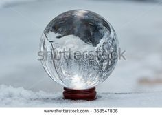 Stock Photo: Winter scene with a transparent crystal ball reflecting the snowy landscape. Icy river appearing upside down on the ball.