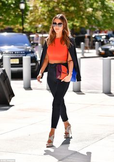 She's got style: In one of the outfits she showed off her toned tum in an orange crop top, which she coupled with a pair of blue high-waisted jeans