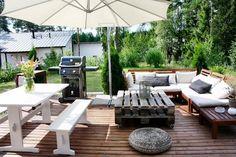 decoration jardin terrasse en bois avec une table basse en palette à roulettes, canapé bois, coin repas en bancs et table blanches, barbecue