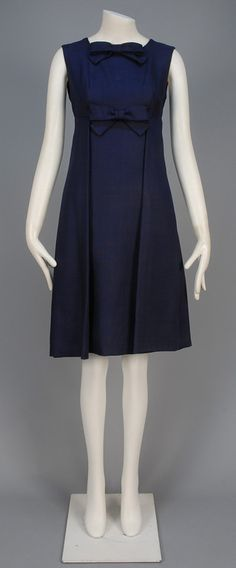 DONALD BROOKS SUMMER DAY DRESS, 1960 - 1965. Sleeveless dark blue linen-look fabric having empire waist, self bows and large pleated front detailing.