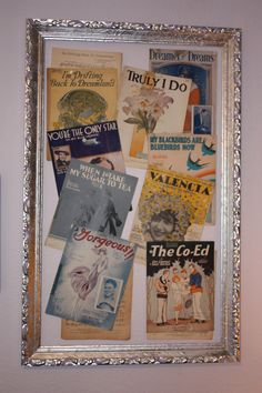 An old frame I spray painted with metallic silver, hung on the wall, placed the sheet music within, using pushpins I had glued buttons on.  I am still going to add old B/W photos and some flowers for dimension.