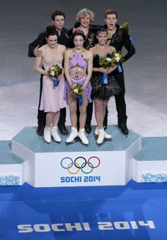 Meryl Davis and Charlie White of the United States, centre, Tessa Virtue and Scott Moir of Canada, left, and Elena Ilinykh and Nikita Katsalapov of Russia stand on the podium during the flower ceremony for the ice dance free dance figure skating finals at the Iceberg Skating Palace during the 2014 Winter Olympics, Monday, Feb. 17, 2014, in Sochi, Russia. Davis and White win Gold, Virtue and Moir win Silver, with Ilinykh and Katsalapov win Bronze.