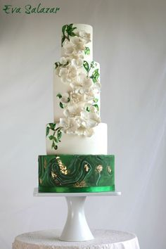 White and green Malaquita wedding cake with hand painted leaves finished with gold accents. Beautiful fondant work!