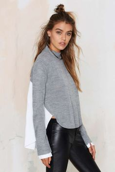 This white top features a gray sweater overlay, ribbing at mock neck and cuffs, and an asymmetric hem.