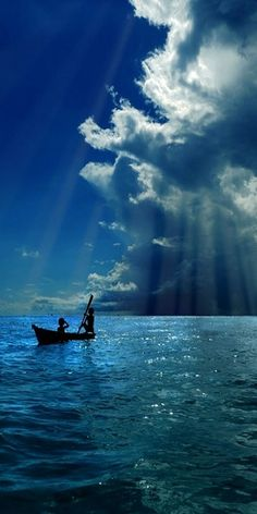 Curtains of blue light descend from the blue clouds onto blue waters, while boatmen watch