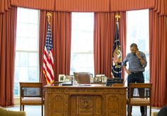 President Obama on the phone in the Oval Office, talking to the russian president Vladimir Putin. March 1, 2014.