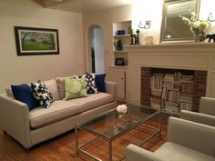 Living room ideas: Crate & Barrel Dryden couch and era coffee table; blues and greens; faux fireplace with books