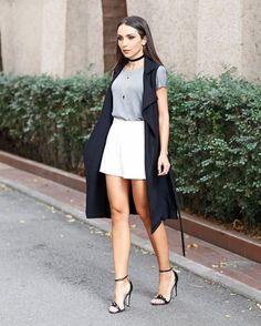 Colete preto, t-shirt cinza, short branco, sandália de duas tiras preta