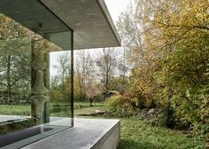 Slabs of concrete frame glass walls of house near a Swiss lake by MLZD.