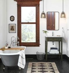 Classic bathroom with black clawfoot tub, single freestanding vanity, and smoked glass pendants