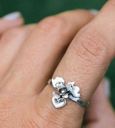 Delicately detailed, like its floral inspiration, this iris ring is completely handcrafted. First, the petals are sawed from sterling silver sheet and textured with melted silver. Then, the petals are layered and curved to form the three-dimensional shape. Each piece is carefully soldered together to form the bloom and finished with a thin ring band.