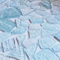 sea glass pieces with white calligraphy. fun idea for name cards at a beach wedding. Green Wedding Shoes on Instagram.