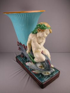 MINTON monumental majolica floor jardiniere in the form of a cherub riding a dolphin terminating in a turquoise trumpet shaped flower vase, designed by Hughes Protat.