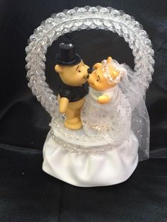 This cake topper contains Winnie the Pooh as a bride and groom. The couple are standing on a base wrapped in white satin and clear beads.