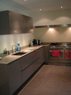 Greige hoogglans keuken met composieten aanrechtblad en hoge kastenwand in bouwkundige nis en - Deco lounge open keuken ...