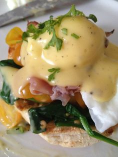 Eggs Benedict Florentine...English muffin half topped with wilted spinach, warmed prosciutto, a poached egg, and drizzled with a homemade Hollandaise sauce and sprinkled with some paprika and parsley!