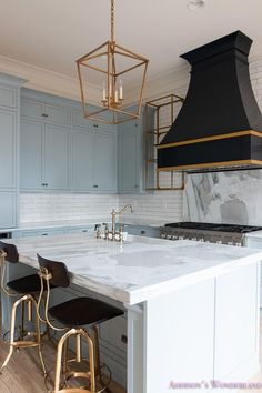 Blue kitchen features blue shaker cabinets painted in a custom color, 50% of Sherwin Williams Stardew and 50% Uncertain Gray, paired with Calcutta Reale Marble countertops and a linear white tile backsplash.