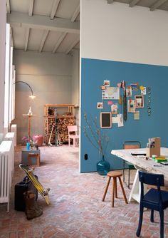 soft blue wall and worn brick floors