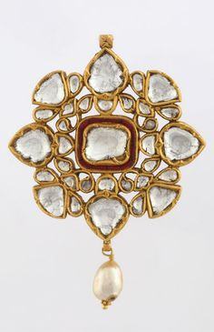 A 'POLKI' DIAMOND PENDANT Of openwork design, kundan-set with large table-cut 'polki' diamonds and rubies, and suspending a single pearl tassel