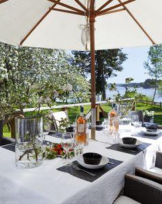 Sommarbordet är duktat med grov linneduk, porslin och cylindervas från Granit.