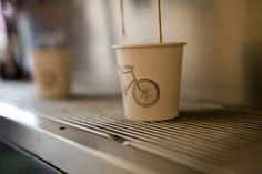 Cups bearing a bike stamp. London coffee shop - signature stamped cups