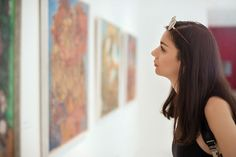 Young woman viewing pictures at an art gallery