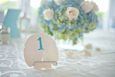 Beach wedding table number made from a real seashell