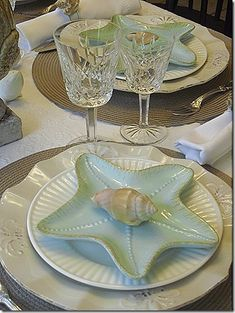 "Lovely setting of white and pale aqua on natural placemats, crystal goblets, showing that ""beachy"" doesn't have to be casual.  Love the starfish shaped dish!"