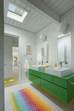 The main bath was remodeled and updated with the kids in mind. A vibrant green sink console and rainbow rug provide a pop of color in the cl...
