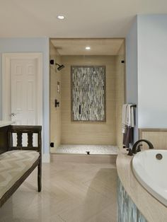 While neutral tones — grays and browns — are the palette in this bathroom, the space is anything but plain. Multiple shapes and colors of tile have been laid in varying, interesting patterns, creating a room that is both harmonious and visually stunning. A bench upholstered with a chevron pattern echoes the floor in the spa-like space.