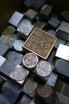 "Chinese chops/seals. These seemed to be a very rare collection that used to stamp on the old paintings. I'm very curious where and when this picture was taken.  Maybe there's a shop made all these ancient-looking chops. The most unusual part about this photo is all the seals seemed to make of metals. The metal ones are usually called ""官印"", which are only used by official institutes like government(in ancient time). The personal ones are usually made of rocks."