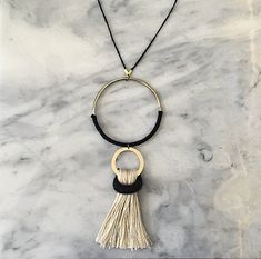 Lovely black and white necklace with double brass circle and tassel detail.
