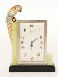 Unknown - French - A 1920's Art Deco rectangular clock in a chrome plated frame with gilt Arabic numerals and bevelled glass front mounted in a stepped green onyx frame raised on a rectangular plinth, the green onyx side with cold painted bronze parrot perched on a ball to one side, the clock movement and dial marked Made In France and the parrot initialled G.L, height 23cm,