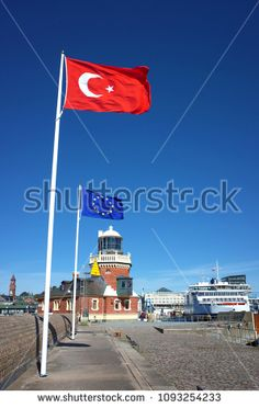 Helsingborg, Sweden - 04 May, 2018: European and Turkish flags flap in the wind at harbour parapet in Helsingborg, Lighthouse and Scandlines ferry also on photo