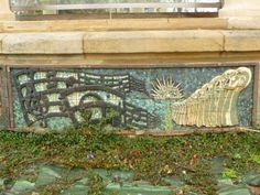 """""""LAGUN ZAHARRAK"""". Mosaico rectangular en tesela cerámica modelado, en relieve,  por Paco Presa Merodio (Torrelavega, 1961 -). Instalado en 2007, fue realizado  en pasta de loza y arcilla roja y decorado con esmaltes y engobes coloreados, cocidos a 1050-1100º C. Se homenajea a la coral Lagun Zaharrak: pentagramas con notación musical en clave de Sol y Fa,  un grupo de personajes cantando, representados con un estilo que se aproxima al Art Deco, inspirado en un cartel de la propia coral."""