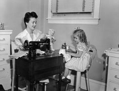 A mother and young daughter sewing garments for a doll - 1955