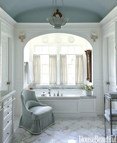 The glossy barrel ceiling in the master bath is painted in Farrow & Ball's Skylight. P. E. Guerin tub fixtures. DeAngelis chair in Empress Satin by Fret Fabrics.