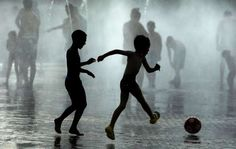 Children play soccer as they cool down in a fountain beside Manzanares river in Madrid on Monday, Ju... - Andres Kudacki/AP