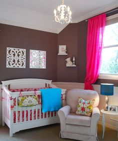 "A vintage nursery with layered patterns, rich colors and crystal accents. Hot pink, turquoise, and robin's egg blue are set against a rich background of chocolate walls with ivory wood wainscoting for an elegant, classic look. Ivory furnishings and artwork were used to ""pop"" against the chocolate backdrop. Floor to ceiling dupioni silk draperies highlight the dramatic 10' ceiling height."