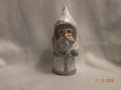 Paper Mache Father Christmas painted in white and silver with glitter. This is one of a kind!  All hand sculpted and made of 70% recycled or reused items. This item is made of a toilet paper role,newspaper, tissue paper and paperclay and is about 7inches tall. Perfect for placing on a mantle or a shelf to celebrate the holidays!   A great gift for you or the Santa Claus lover in your life