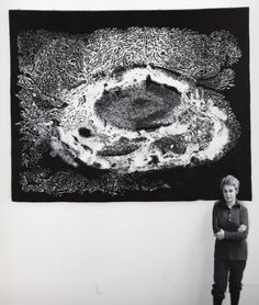 June Wayne, in front of her tapestry, At Last A Thousand. 1971. Two examples, woven by Pierre Daquin, Atelier de Saint Cyr, with the artist's signature woven lower left.   This tapestry is based on the quartet of Wayne lithographs published by Tamarind in 1965 in honor of its thousandth edition.