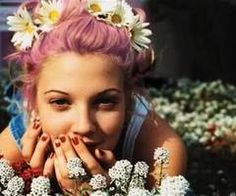 Drew Barrymore looks incredible. A serial 90s photo. Drew wearing overalls and red nail polish accessorizing with thin eyebrows, and babies breath. Lovely pink hair with live daisies adorning her hair.