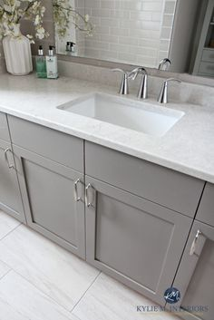 Bathroom vanity painted Metropolis Benjamin Moore gray. Caesarstone Bianco Drift greige quartz countertop, Moen Glyde faucet and porcelain tile flooring by Kylie M Interiors