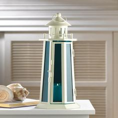 Style ahoy! This nautical candle lantern will wash your living space with a wave of sea blue glow unlike anything youve ever seen. The brilliant ocean blue glass panels stand tall inside the metal lig